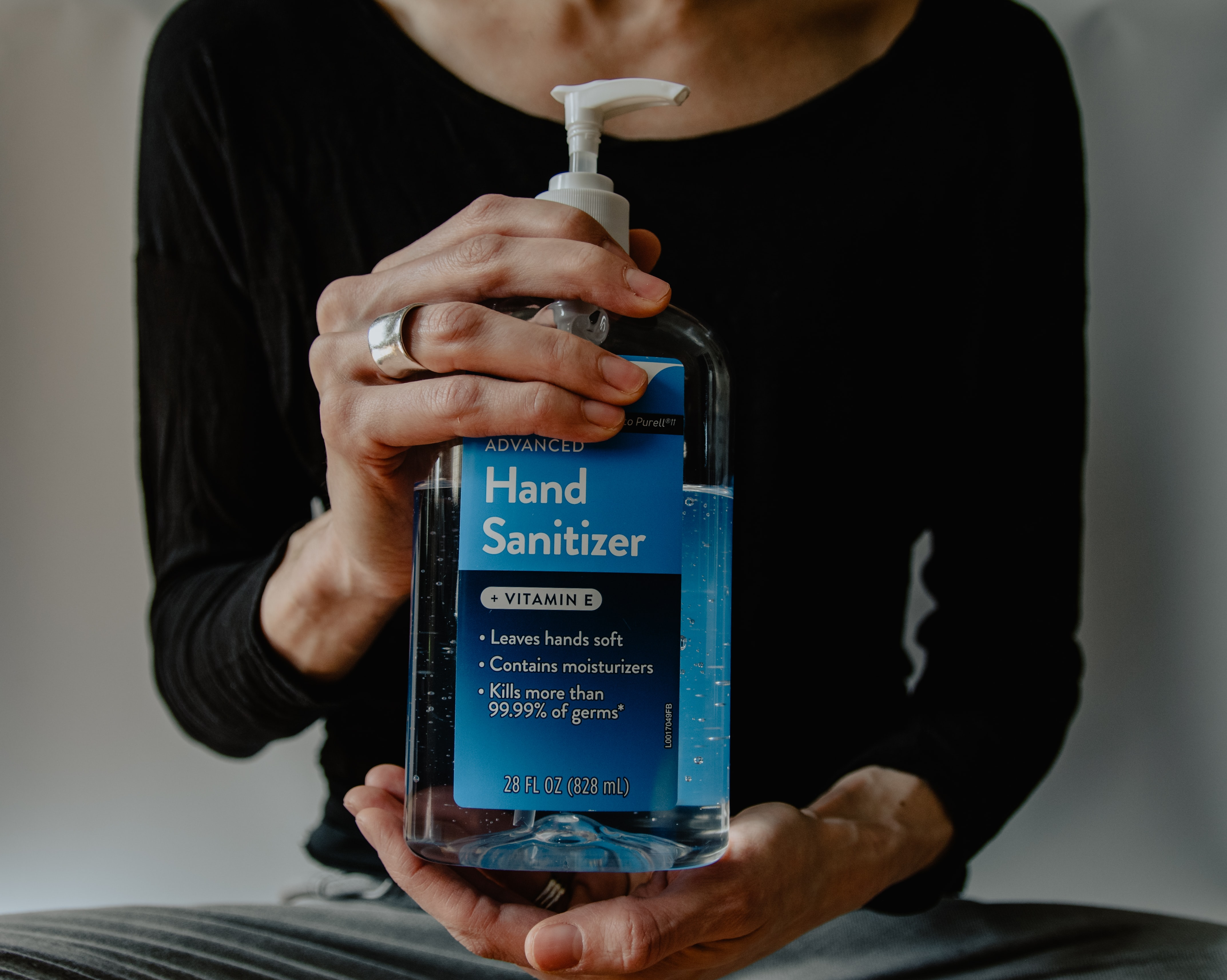 woman holding a bottle of hand sanitizer