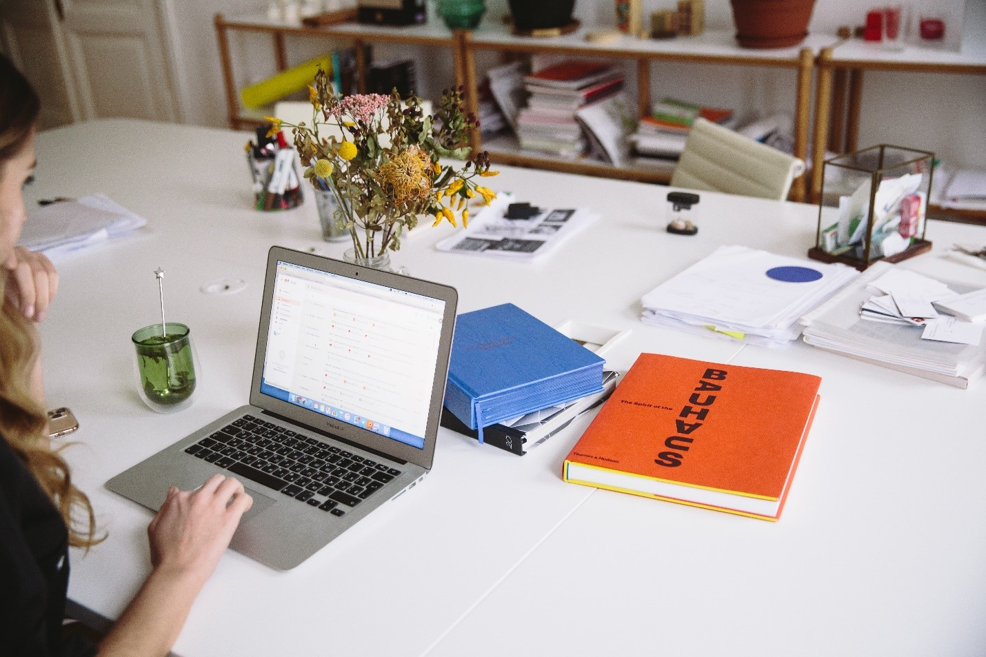 woman using laptop on white table with books scattered around