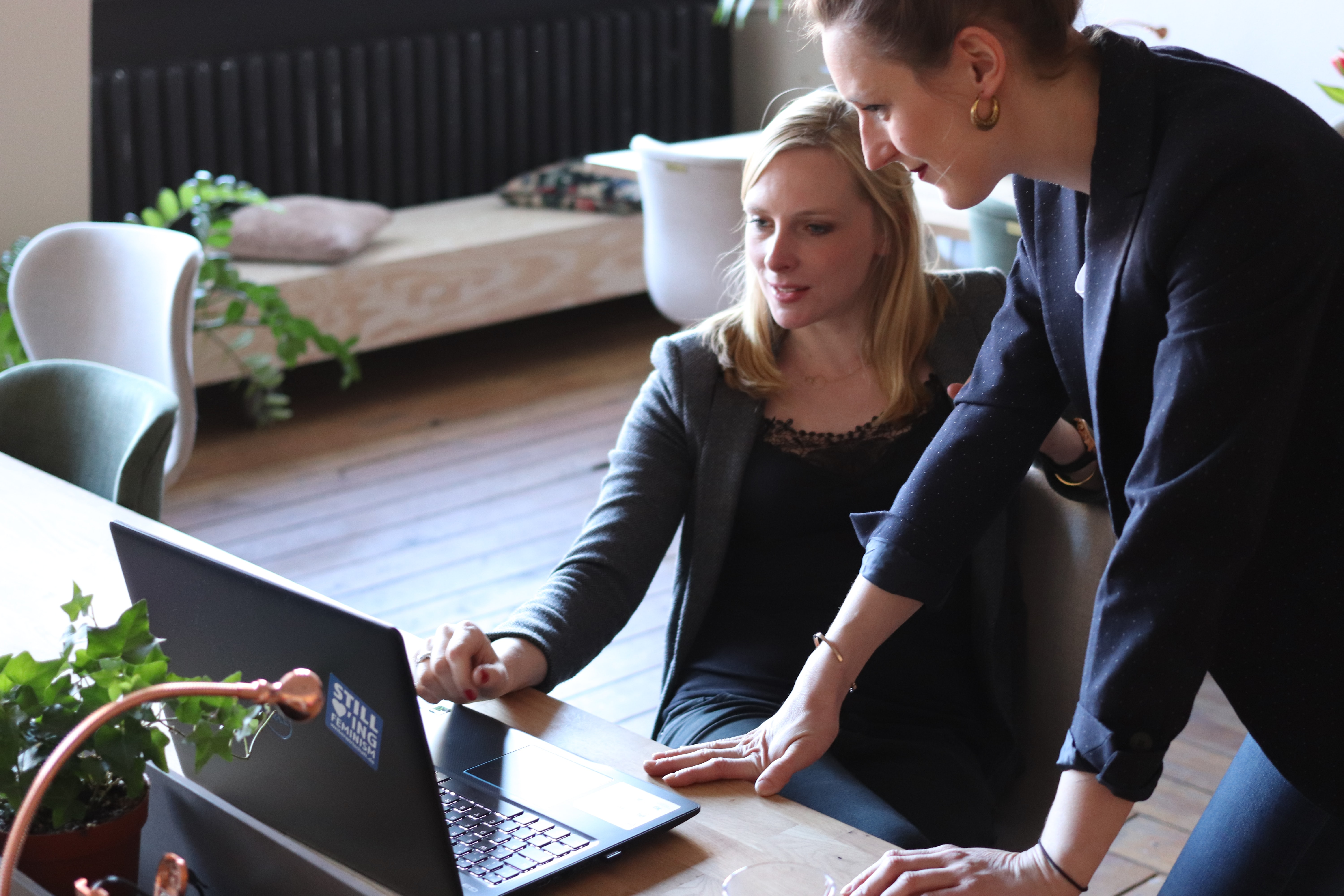 employee sharing laptop screen with coworker