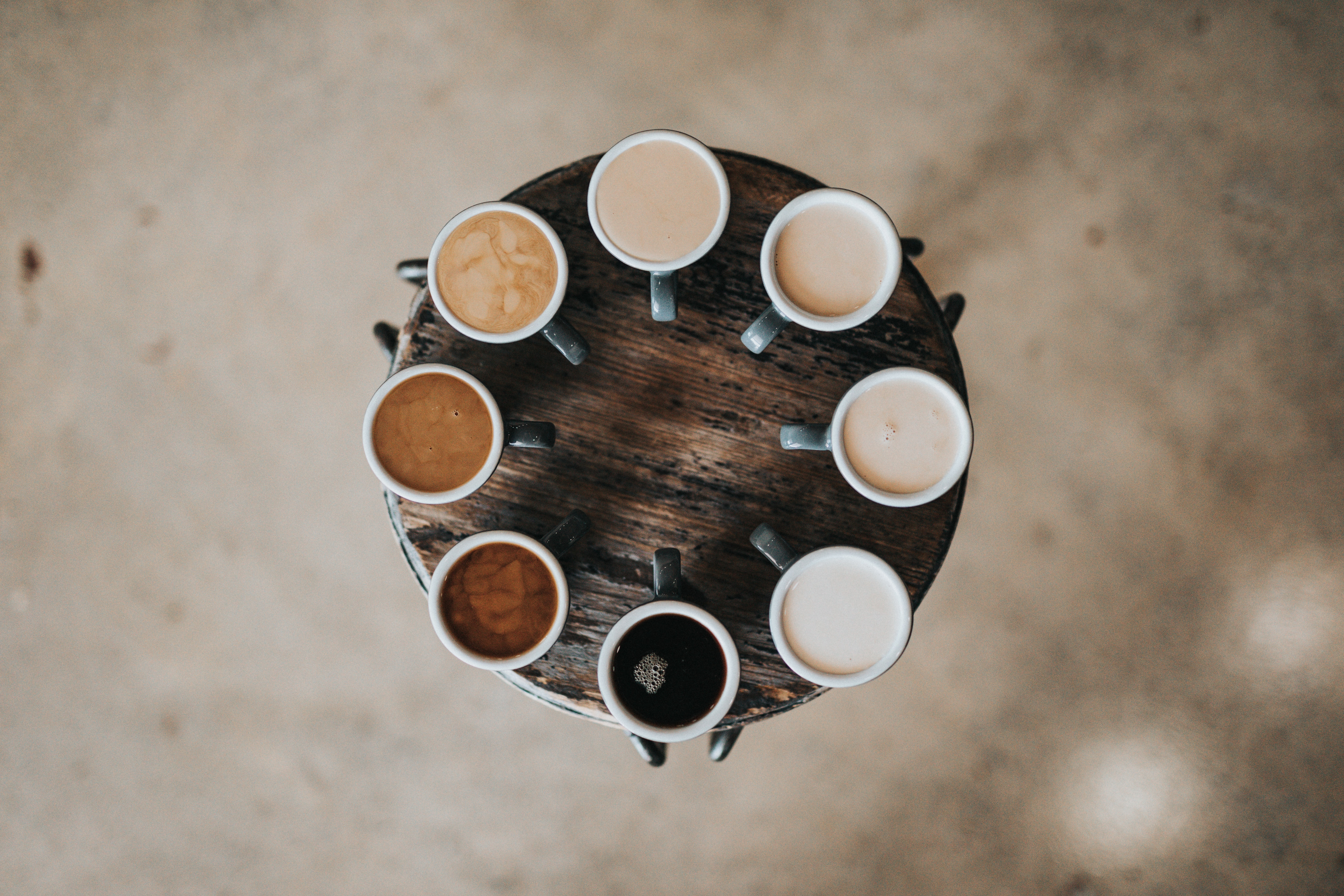 coffee cups ranging in color, from black coffee to milky-white liquid, representing diversity