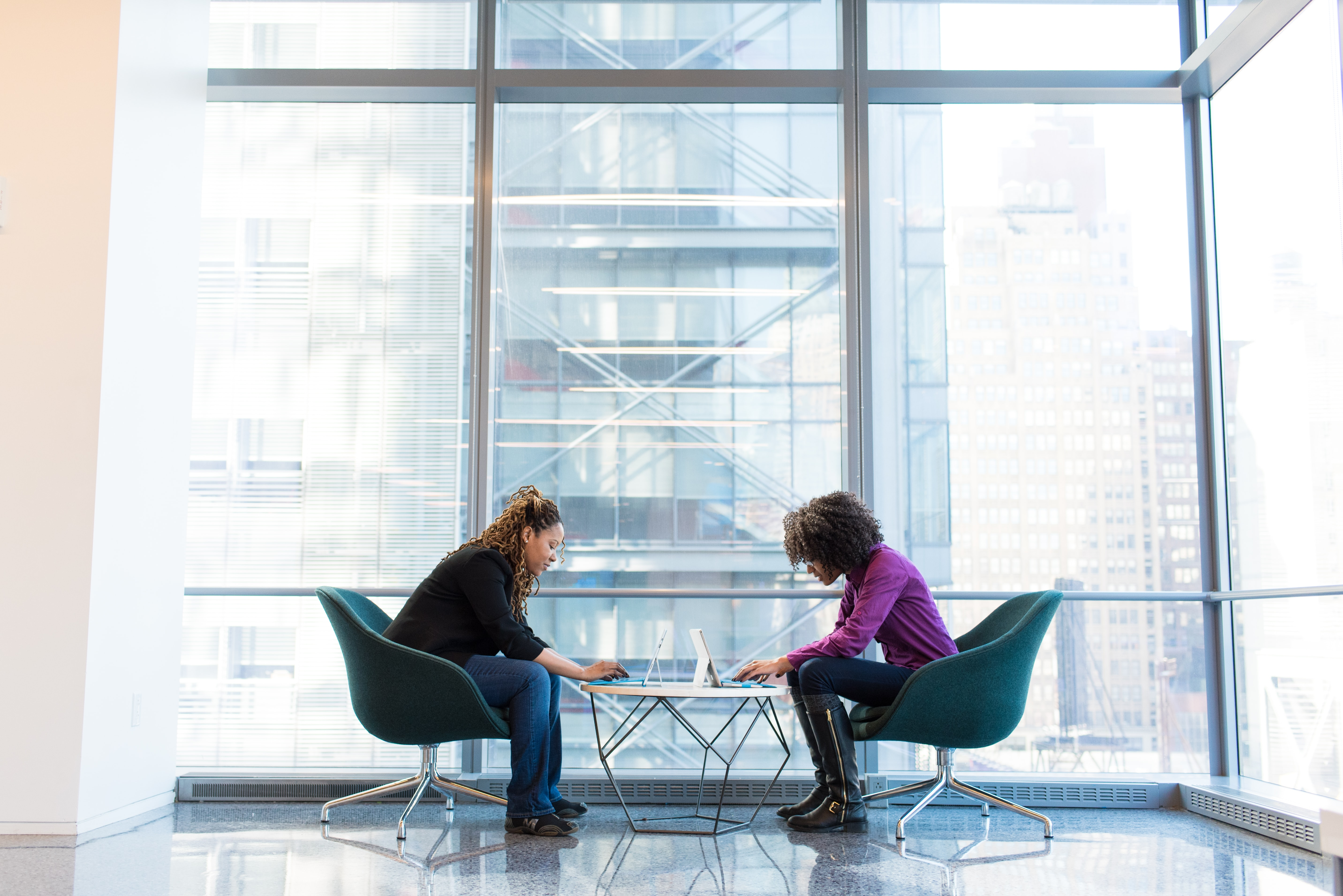 two women sitting across from each other in an office