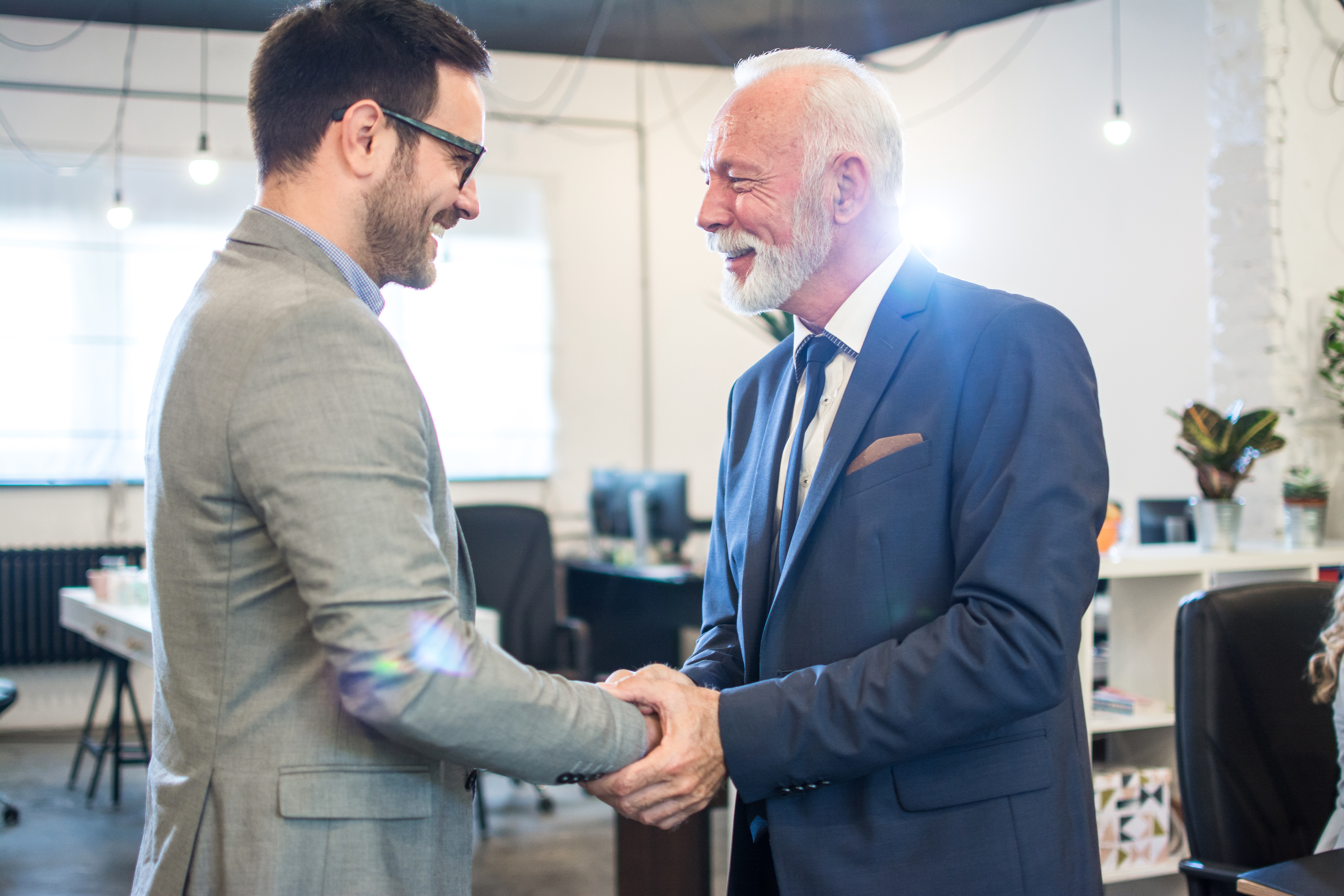older man shaking a younger man's hand in an office
