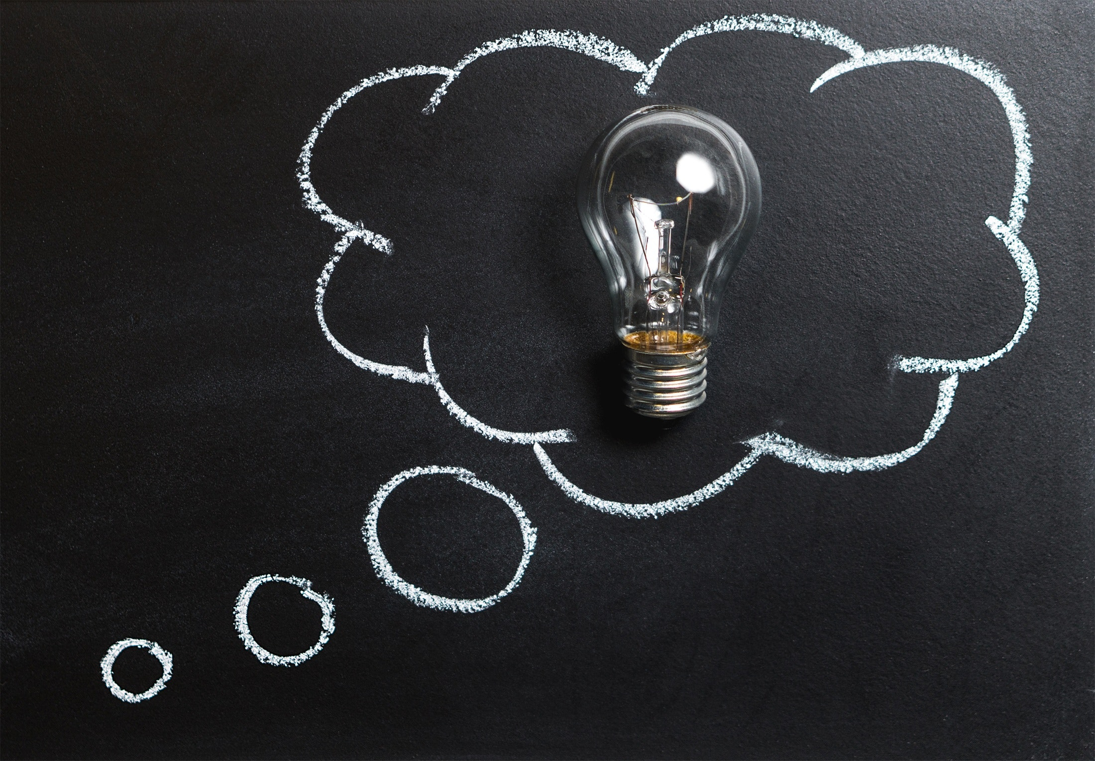 A chalkboard with a thought bubble holding a lightbulb