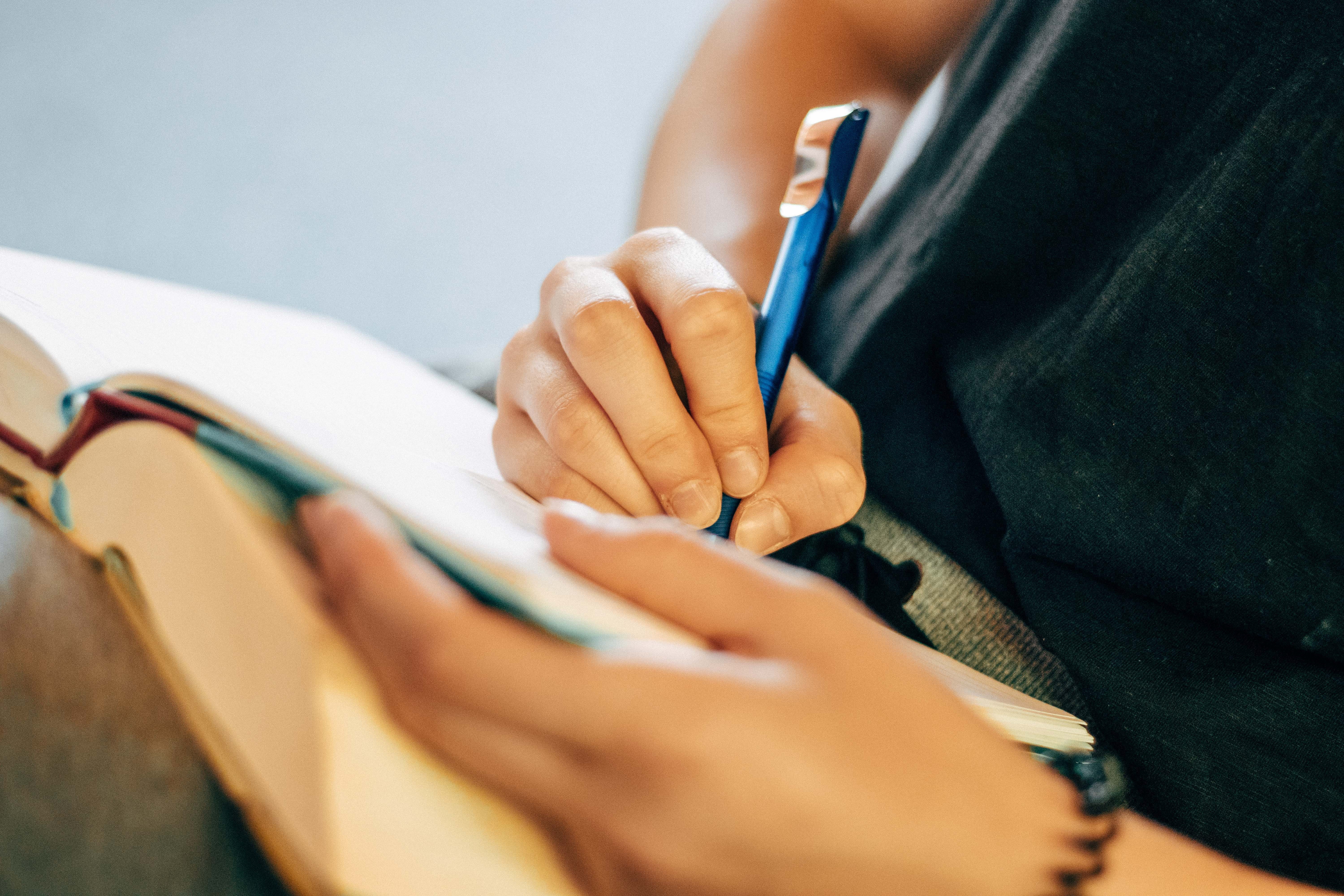 person taking notes in notebook