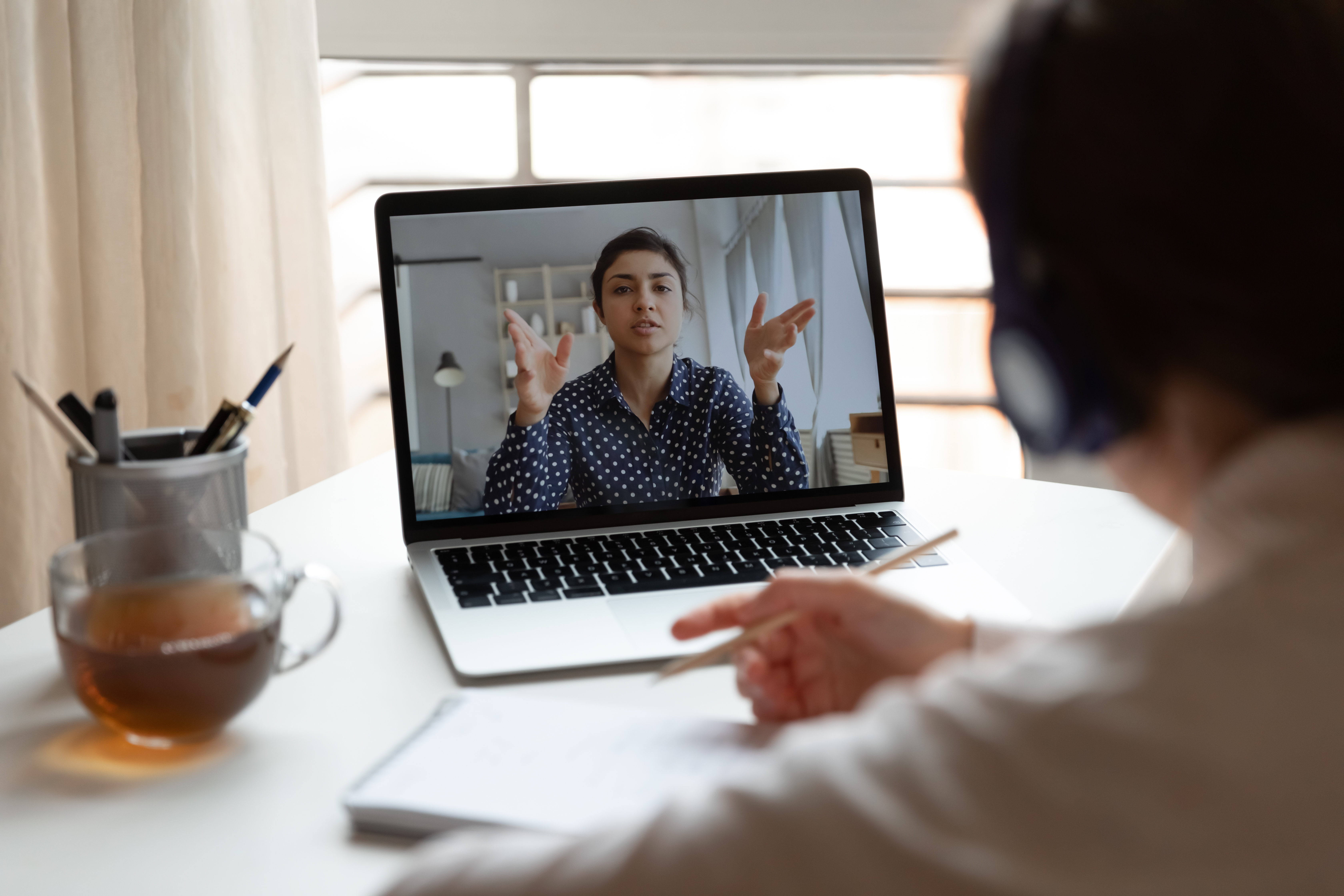 A professional watching a virtual instructor-led training course on a laptop computer