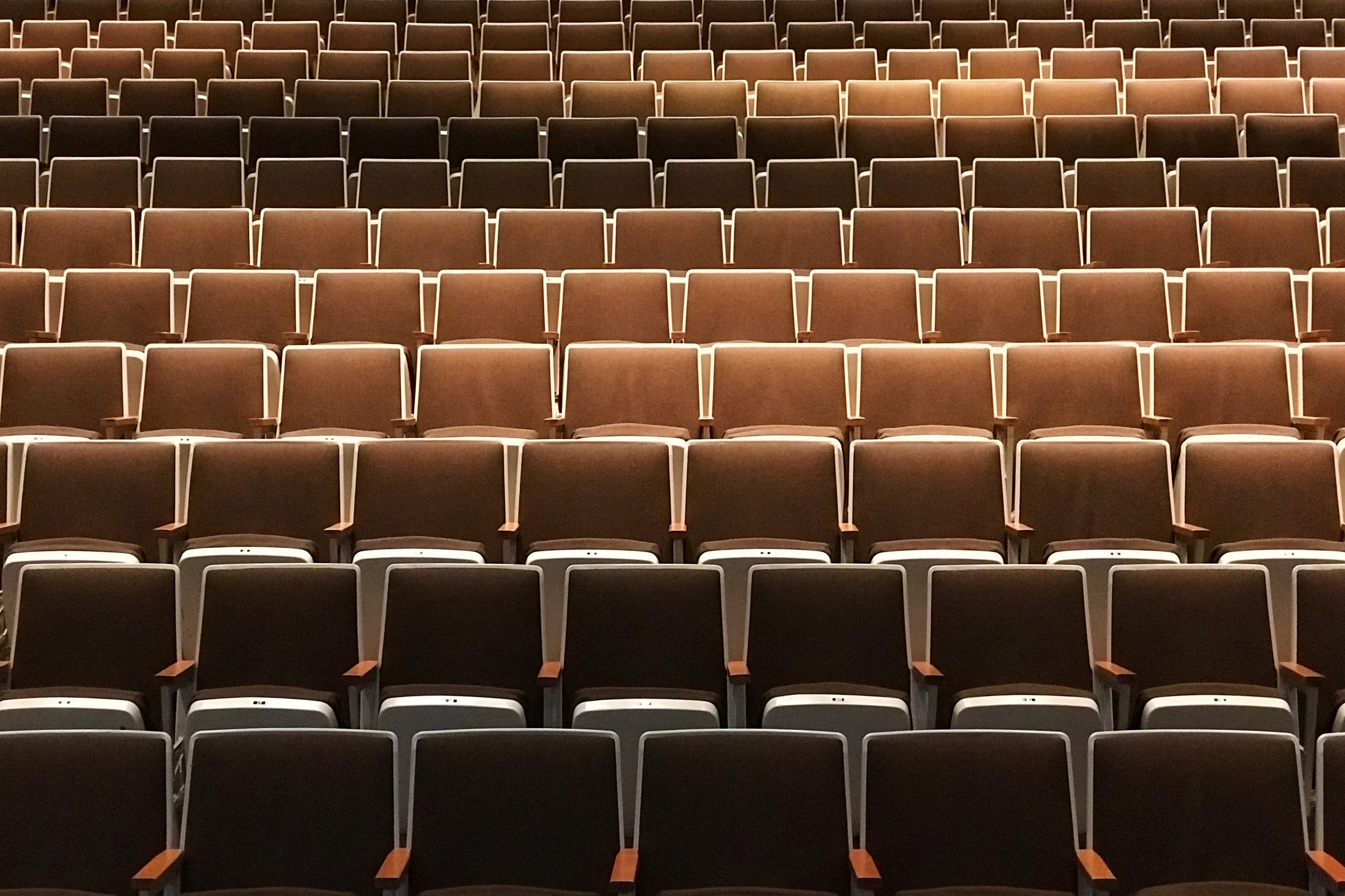 Empty brown leather seats in a large auditorium