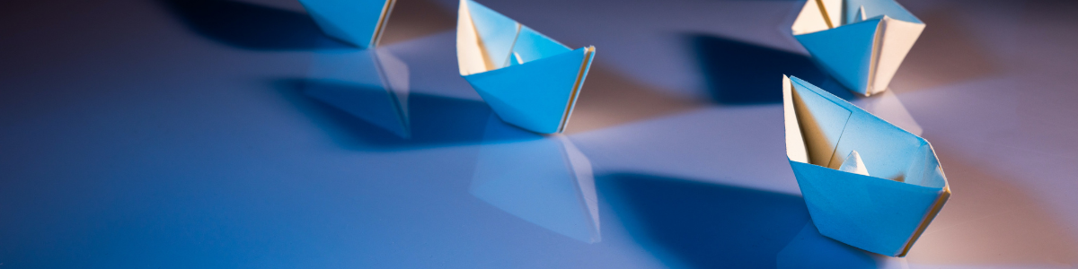Paper boats with one in front, symbolizing leadership