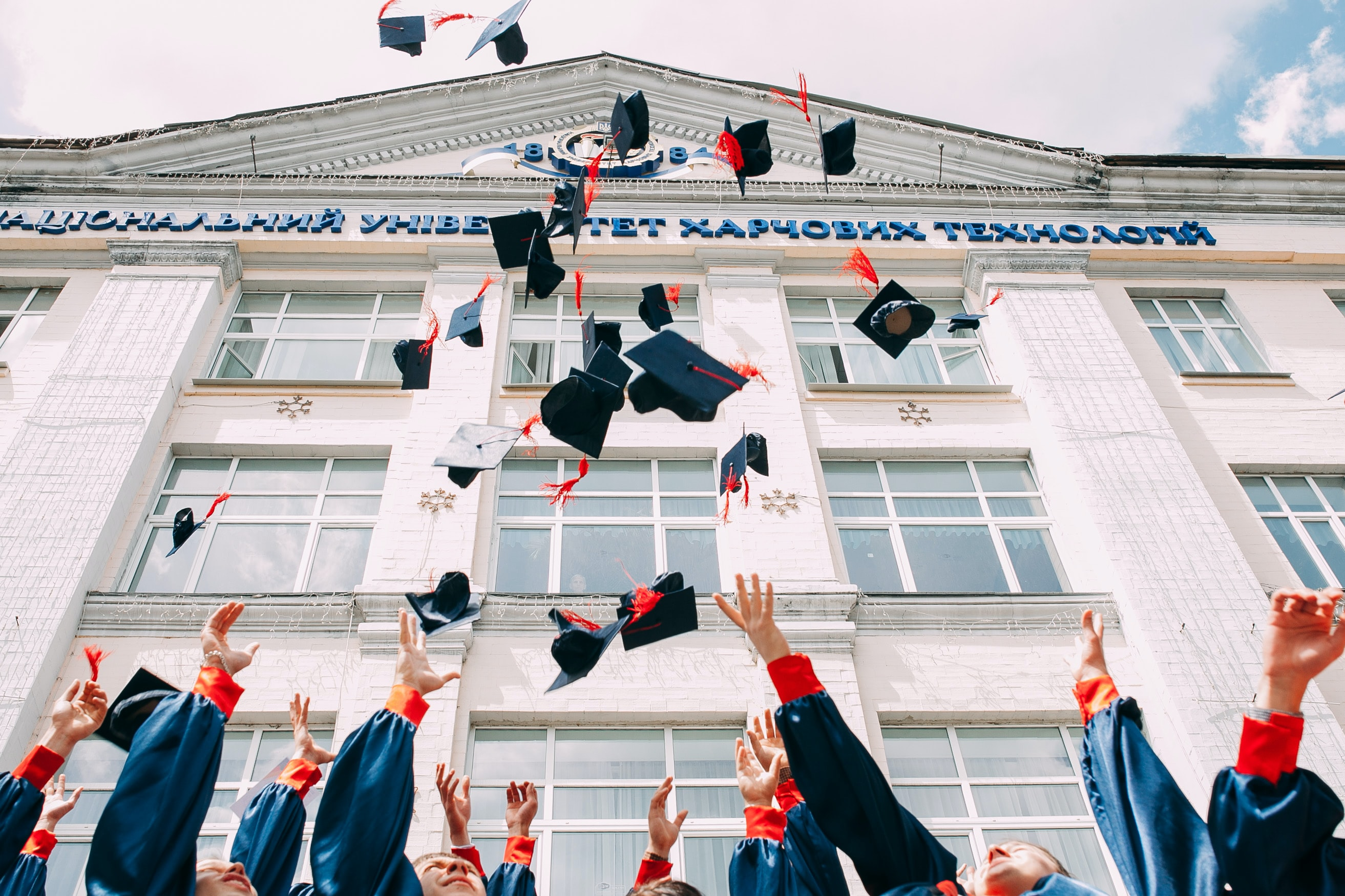 Students throwing their graduation caps in the air in front of a university building