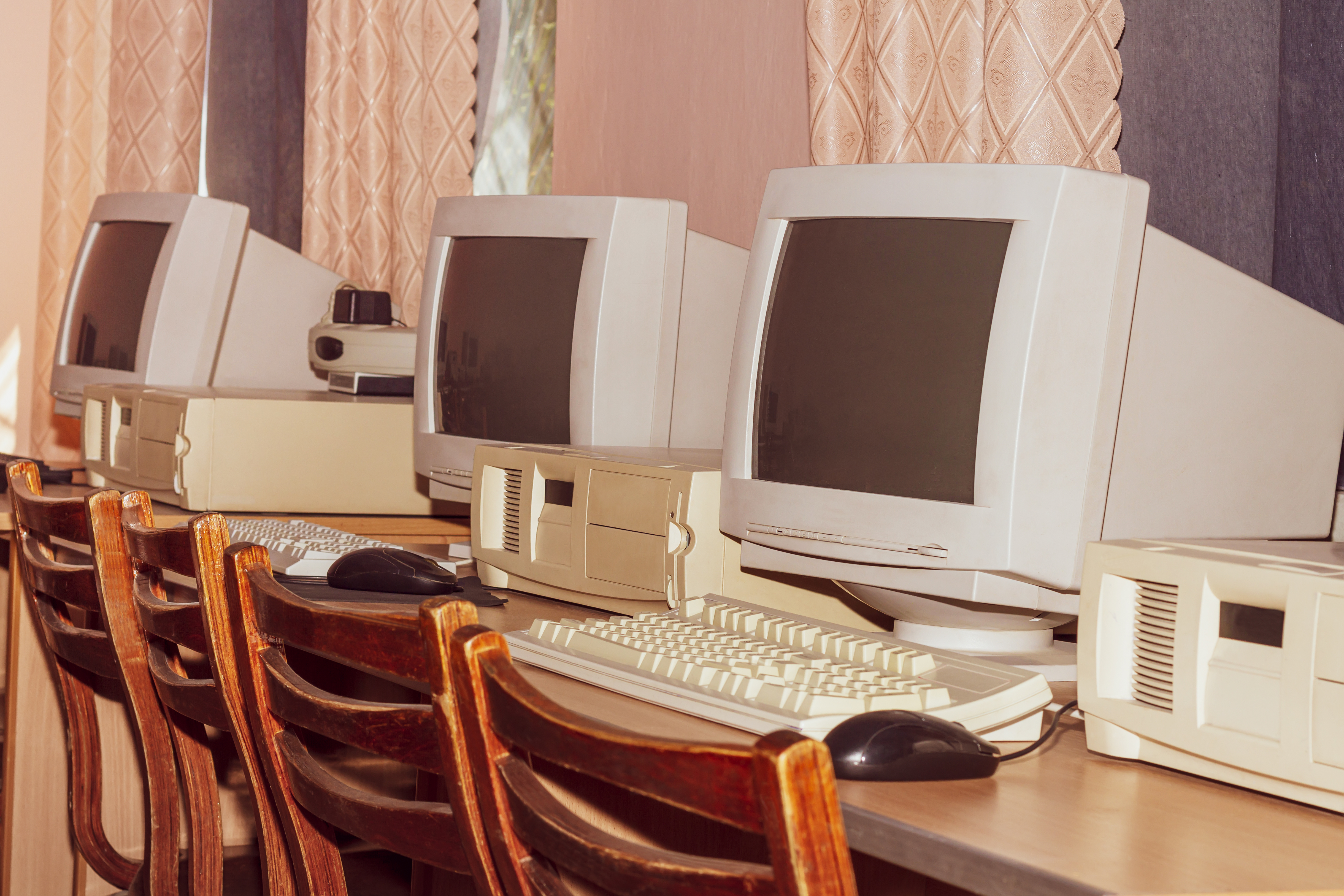 three vintage desktop computers from the 1990s on a wood table