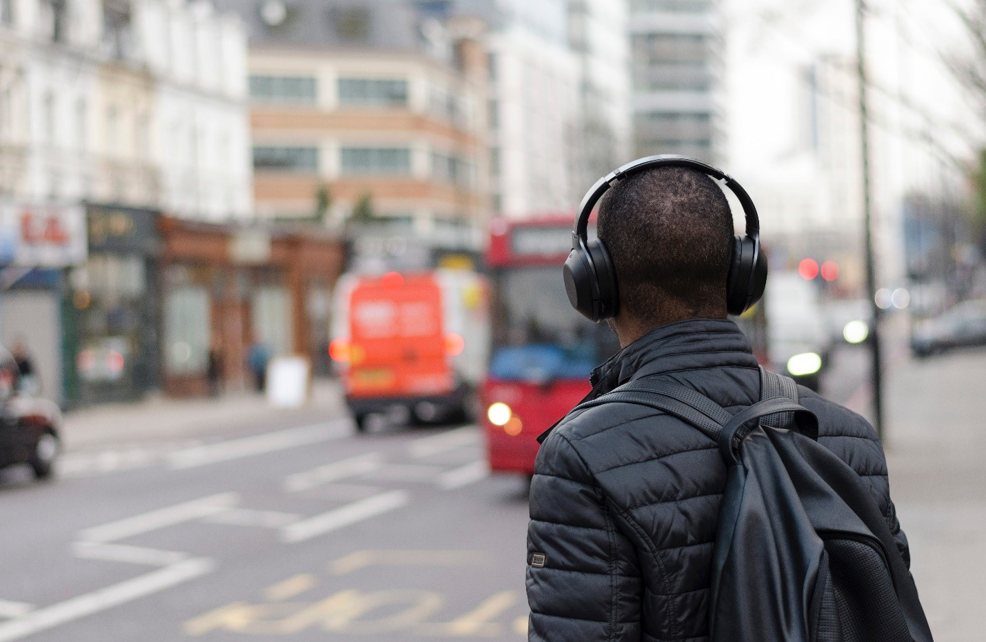 man standing on busy city street with headphones on